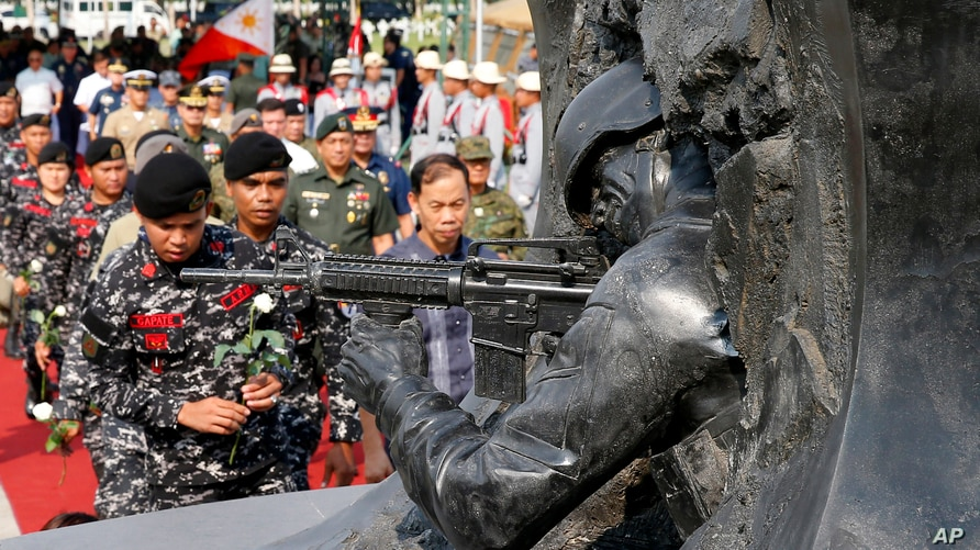Philippine troops prepare to lay white roses at the Marawi Memorial pylon for fellow soldiers killed in the five-month siege of…