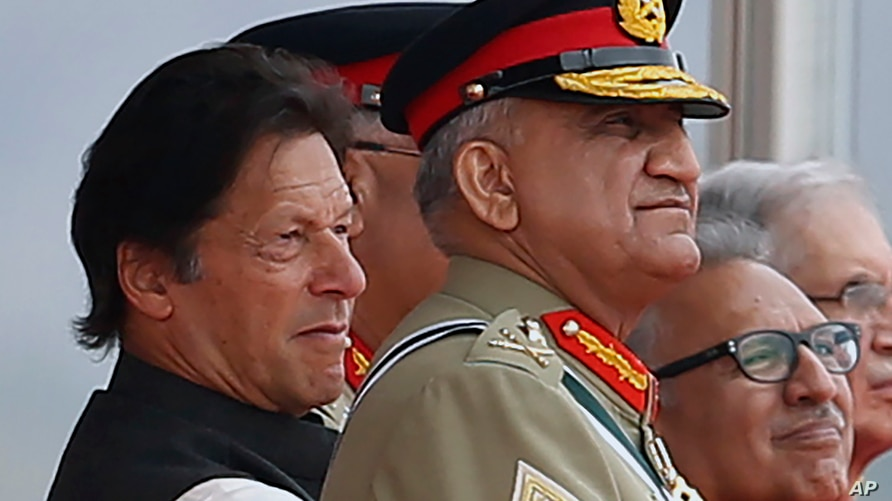 FILE - Pakistan's Army Chief Gen. Qamar Javed Bajwa, center, watches a parade with Prime Minister Imran Khan, left, and President Arif Alvi, in Islamabad, Pakistan, March 23, 2019.