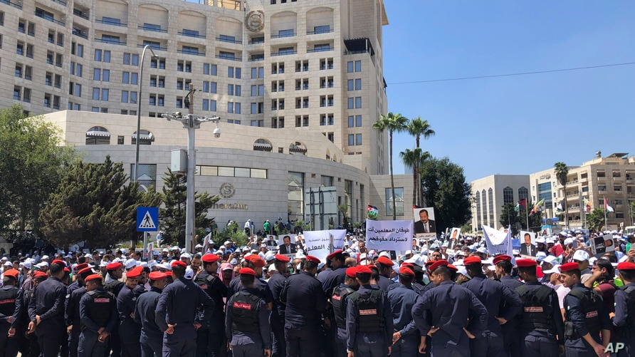 FILE - Security forces block a road as teachers protest in Amman, Jordan, Sept. 5, 2019. Thousands of Jordanian teachers held a protest demanding higher wages, with some scuffling with security forces.