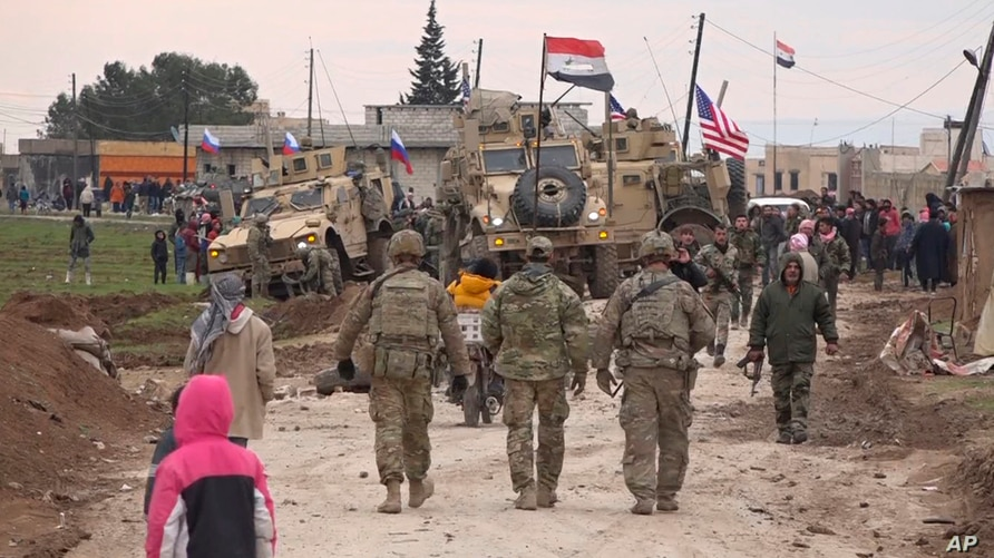 In this frame grab from video, Russian, Syrian and others gather next to an American military convoy stuck in the village of…