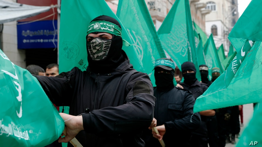 Masked Hamas militants wave their green flags during a protest against the Mideast plan announced by U.S. President Donald…