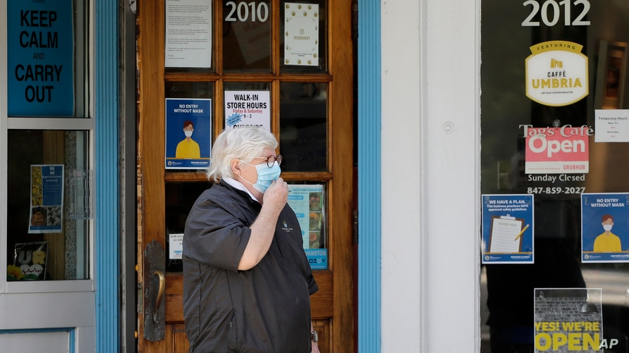 A woman wears mask as she walks past a opened sign cafe in Evanston, Ill., Friday, May 29, 2020. Every region of Illinois met…