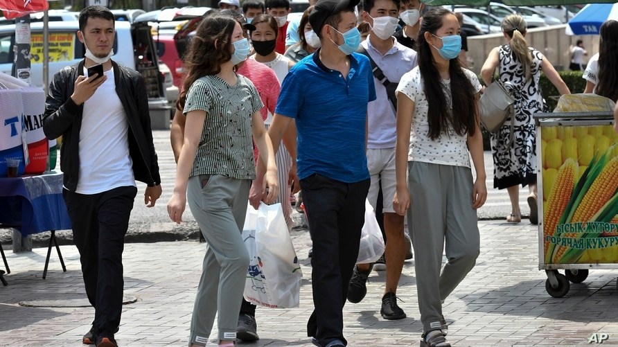 Youths in face masks walk through a street market in Bishkek, Kyrgyzstan, Friday, July 24, 2020. Coronavirus cases surged in…