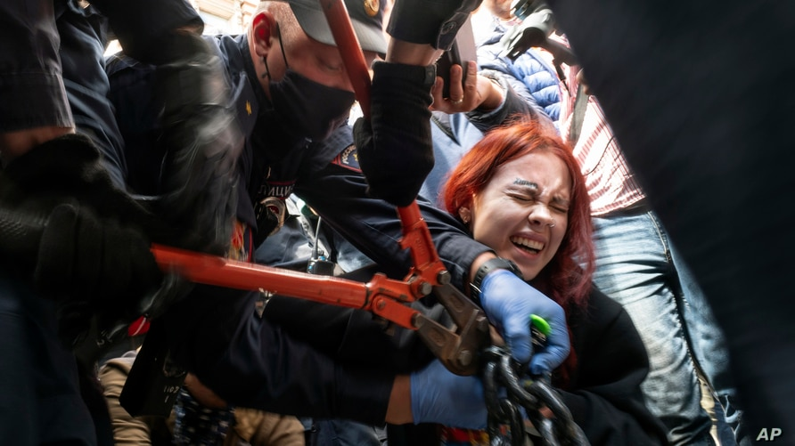 Police try to cut the handcuffs off a woman who handcuffed herself to a fence during a rally supporting Khabarovsk region's…
