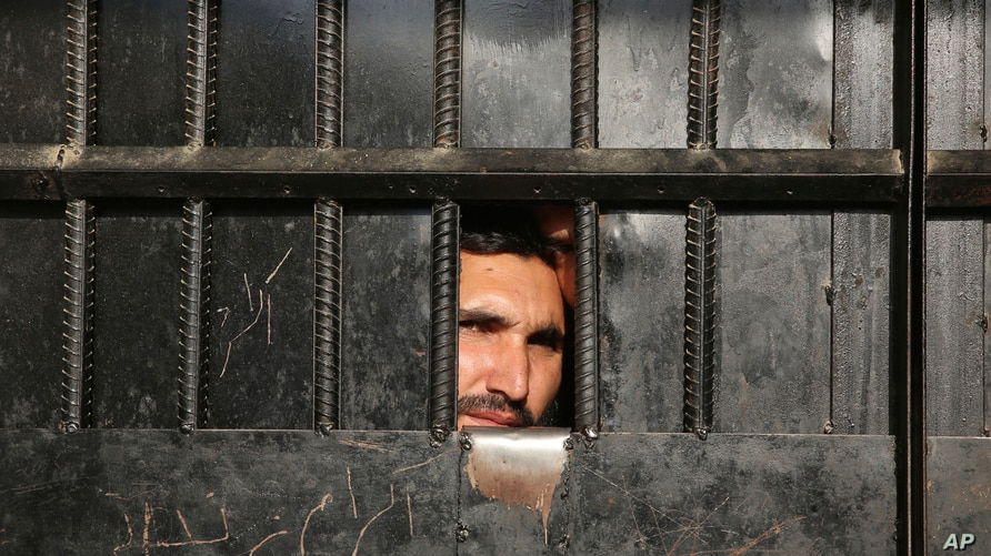 Taliban prisoners watch through the door inside a prison after an attack in the city of Jalalabad, east of Kabul, Afghanistan,…