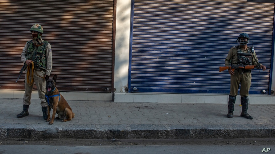 Paramilitary soldiers stand guard on a deserted street on the first anniversary of India's decision to revoke the disputed region's semi-autonomy, in Srinagar, Indian controlled Kashmir, Aug. 5, 2020.