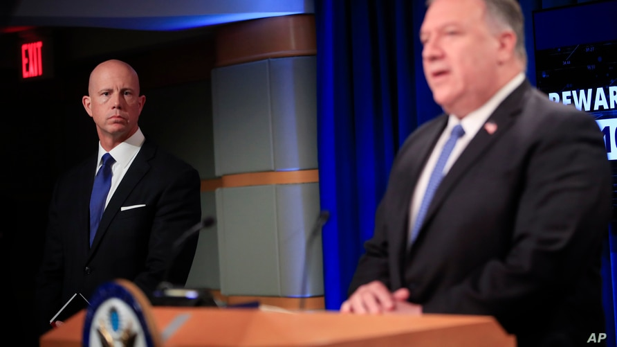 State Department Deputy Spokesperson Cale Brown, left, listening to Secretary of State Mike Pompeo, right, speak during a news…