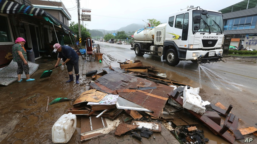 Residents scrape mud away from a damaged house following heavy rains in Cheorwon, South Korea, Aug. 6, 2020.