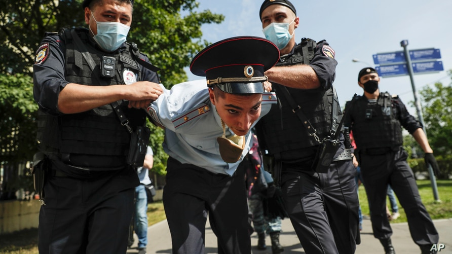 Police officers detains a protester, center, dressed as a Russian police officer before a court hearing of the New Greatness group who are charged with the organization of an extremist association in Moscow, Russia, Aug. 6, 2020.