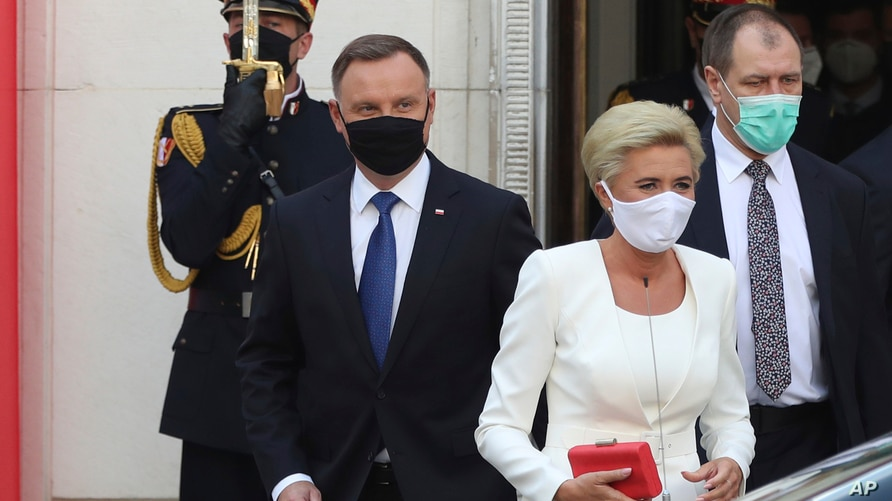 Poland's conservative President Andrzej Duda,left, and First Lady Agata Kornhauser-Duda, right leave the parliament building following the ceremony of Duda's swearing in for a second five-year term in Warsaw, Poland, August 6, 2020.
