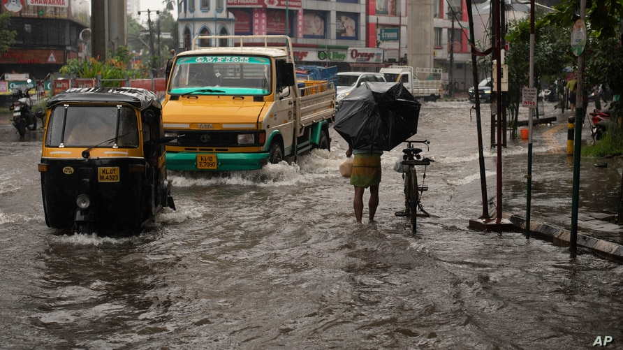 Vehicles move through a waterlogged street during heavy rainfall in Kochi, Kerala state, India, Aug. 7, 2020.