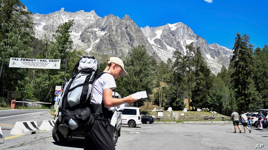 A hiker looks at a map as he walks in a parking lot beneath the Planpincieux glacier, seen at background right, in the Alps on the Grande Jorasses peak of the Mont Blanc massif, in Val Ferret, near Courmayeur, northern Italy, Aug. 7, 2020.