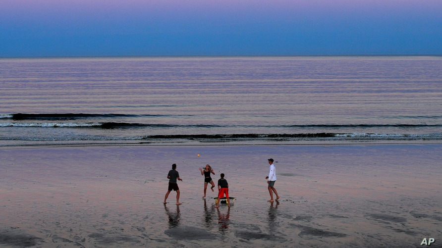 A group of people play Spikeball at twilight on the beach, Thursday, Aug. 7, 2020, in Ocean Park, Maine. As the summer tourist…