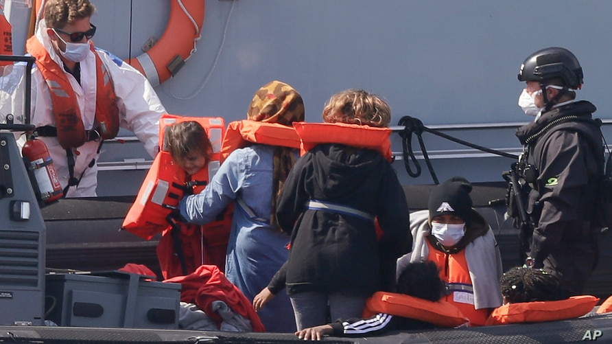 A Border Force vessel brings a group of people thought to be migrants into the port city of Dover, England, from small boats, Aug. 8, 2020.