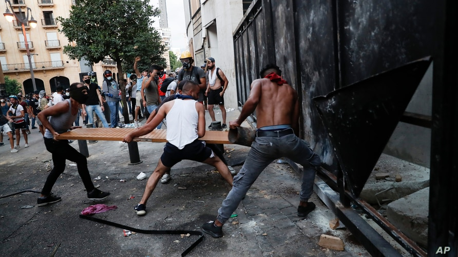 People try to break police barrier during a protest following last week's explosion that killed many and devastated the city, in Beirut, Lebanon, Aug. 11, 2020.