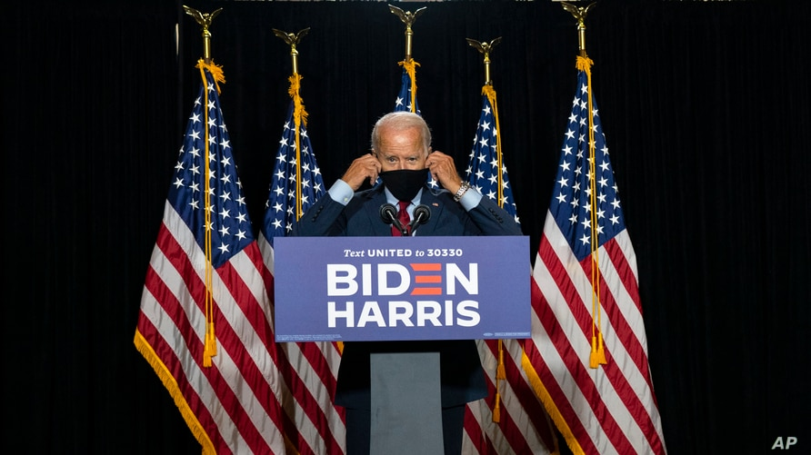 Democratic presidential candidate former Vice President Joe Biden removes his face mask as he arrives to speak