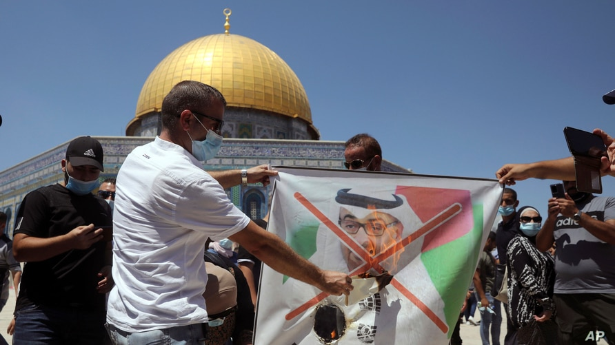 Palestinian protesters burn a banner showing Abu Dhabi Crown Prince Mohamed bin Zayed al-Nahyan during a protest