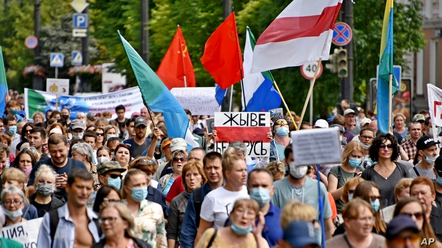 "People carrying a poster reading ""Long Live Belarus"", and an old Belarusian national flag, march during an unsanctioned protest in support of Sergei Furgal, the governor of the Khabarovsk region, Russia, Aug. 15, 2020."