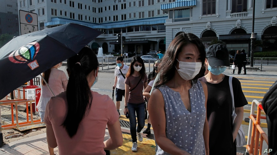 People wearing masks to protect against the coronavirus, walk across a street in Hong Kong, Thursday, Aug. 20, 2020. (AP Photo…