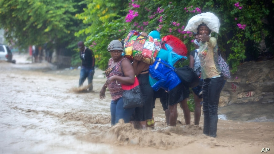 People cross a flooded street during the passing of Tropical Storm Laura in Port-au-Prince, Haiti, Aug. 23, 2020.