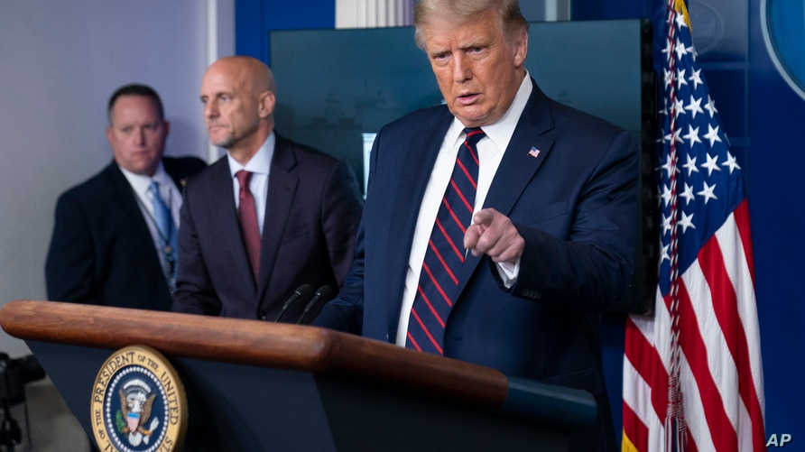 President Donald Trump speaks, accompanied by Food and Drug Administration Commissioner Dr. Stephen Hahn, center, during a media briefing in the James Brady Briefing Room of the White House, Aug. 23, 2020, in Washington.