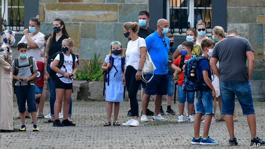 FILE - In this Wednesday, Aug. 12, 2020 file photo, parents wait with children on the schoolyard for the start of their first…