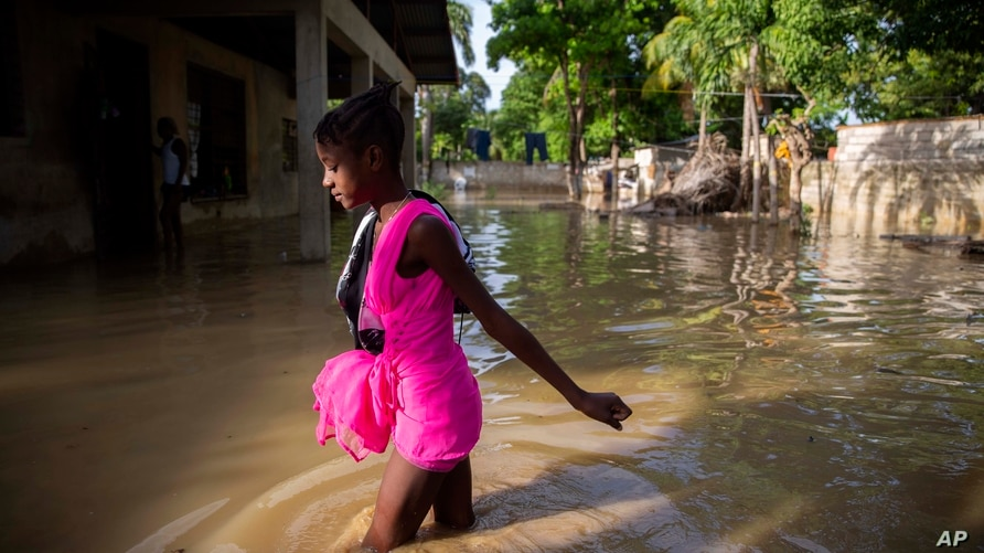 A girl wades towards her flooded home the day after the passing of Tropical Storm Laura in Port-au-Prince, Haiti, Aug. 24, 2020.