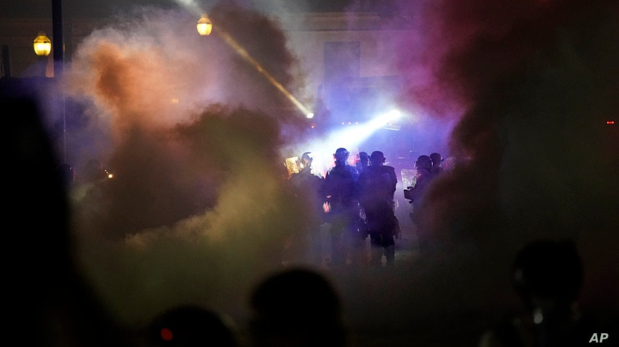 Police in riot gear clear the area in front of Kenosha County Courthouse during clashes with protesters late Tuesday, Aug. 25,…