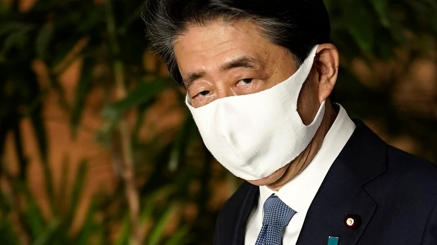 Japan's Prime Minister Shinzo Abe wearing a face mask walks after his press conference at Prime Minister's office Friday, Aug…