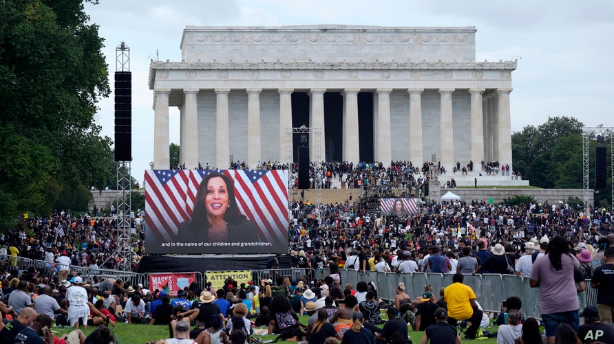 A screen displays a video with Democratic vice presidential candidate Kamala Harris speaking during the March on Washington,…
