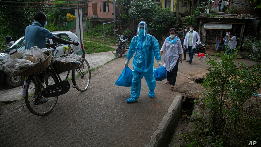 A health worker walks during a door-to-door drive to take nasal swab samples to test for COVID-19 in Gauhati, India, Aug. 29, 2020.