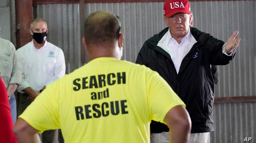 President Donald Trump speaks with first responders as he tours a warehouse being used as a distribution point for relief aid…