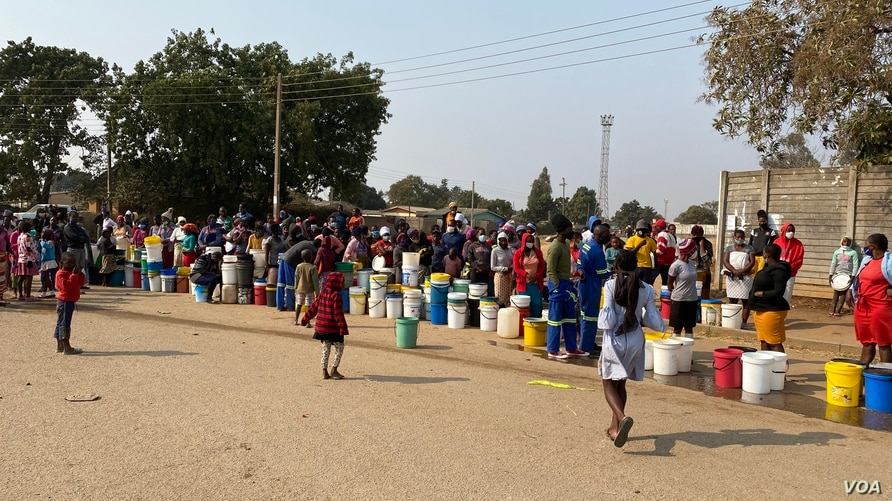 People in Harare forget about social distance to contain coronavirus and get crowded while waiting for free water deliveries from well wishers like Clean City, Aug. 20, 2020. (Columbus Mavhunga/VOA)