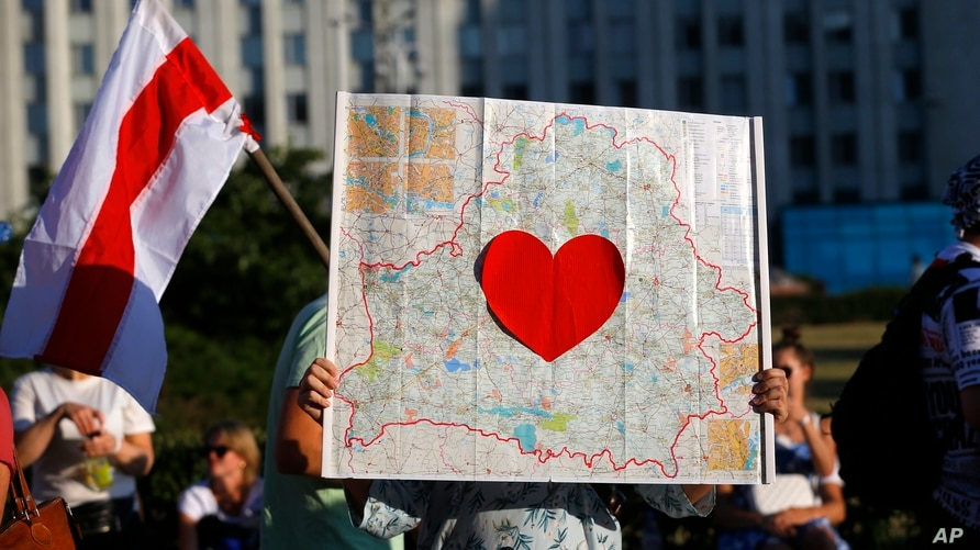 FILE - A protester holds up a map of Belarus with a red heart inside, during an opposition rally in front of a government building in Minsk, Belarus, Aug. 17, 2020.