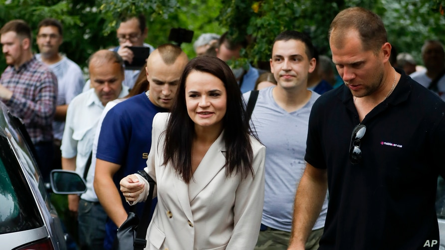 Sviatlana Tsikhanouskaya, candidate for the presidential elections, center, after voting at a polling station in Minsk, Belarus, Aug. 9, 2020.