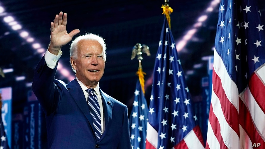 Democratic presidential candidate former Vice President Joe Biden waves as stands on stage on the third day of the Democratic National Convention, at the Chase Center in Wilmington, Delaware, Aug. 19, 2020.