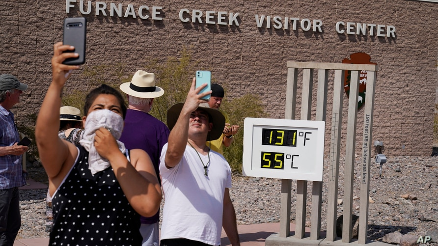 People take selfies at the Furnace Creek Visitor Center thermomete, Aug. 17, 2020, in Death Valley National Park, California.
