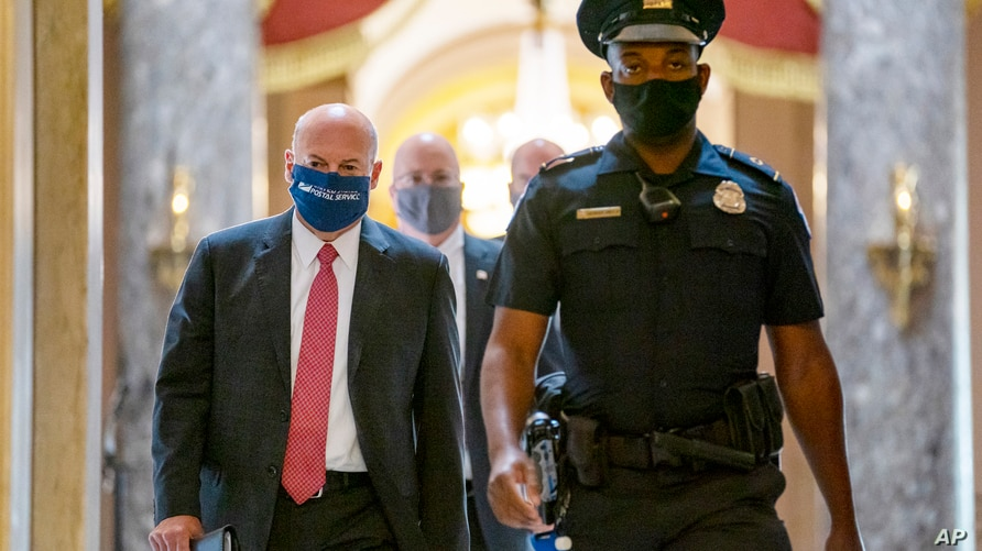 FILE - U.S. Postmaster General Louis DeJoy, left, is escorted to a meeting in House Speaker Nancy Pelosi's office on Capitol Hill in Washington, Aug. 5, 2020.