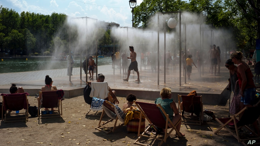 People cool off under a fountain along the Canal de l'Ourcq in Paris, France.
