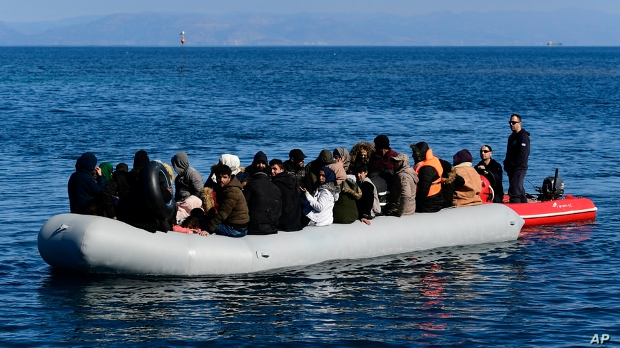 FILE - A Greek Coast Guard boat intercepts a dinghy with migrants near the Greek island of Lesbos, after it crossed the Aegean Sea from Turkey, March 1, 2020.