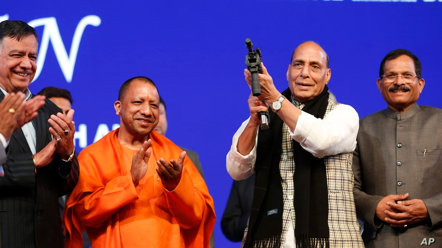 FILE - Indian Defense Minister Rajnath Singh holds a model of a light machine gun with Chief Minister of Uttar Pradesh state Yogi Adityanath, 2nd left, during DefExpo20 in Lucknow, Feb. 7, 2020.