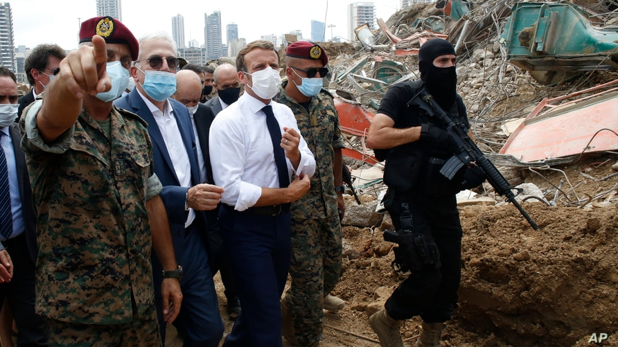 French President Emmanuel Macron, center, visits the devastated site of the explosion at the port of Beirut, Lebanon, Aug.6, 2020.