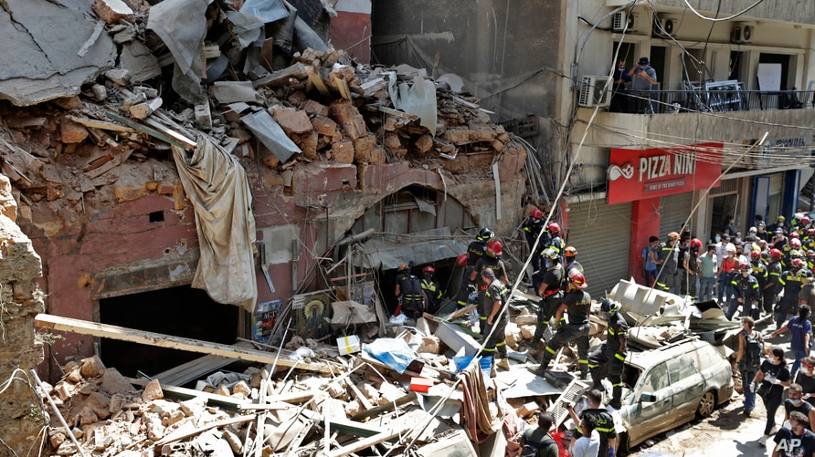 French and Lebanese firemen search in the rubble of a building after the Tuesday explosion at the seaport of Beirut, Lebanon, Aug. 6, 2020.