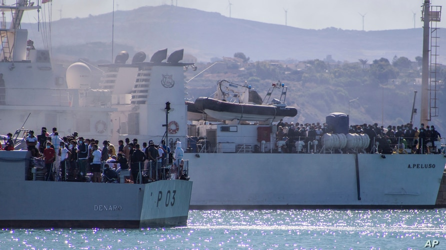 FILE - Migrants arrive in Porto Empedocle, Sicily, aboard two military ships after being transferred from the island of Lampedusa, where a number of small boats carrying migrants arrived a few days earlier, July 27, 2020.
