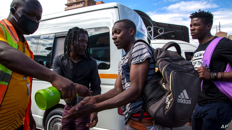 FILE - A taxi marshall wearing a face mask sprays sanitizer on passengers' hands to protect against coronavirus, at a minibus taxi station in Johannesburg, South Africa, March 26, 2020.