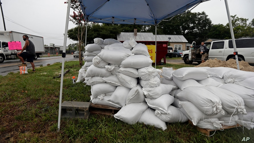 A man, far left, sells sandbags as Hurricane Isaias approaches, in Wilmington, North Carolina, Aug. 3, 2020.