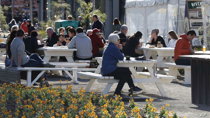 Patrons enjoy lunch at a market in Christchurch, New Zealand, Aug. 9, 2020, as the country marked 100 days of being free from the coronavirus, with just a few infections continuing to be picked up at ports of entry where people are quarantined.