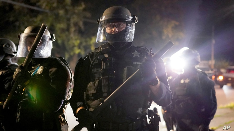 Portland police officers walk through the Laurelhurst neighborhood after dispersing protesters from the Multnomah County Sheriff's Office early in the morning, Aug. 8, 2020 in Portland, Oregon.