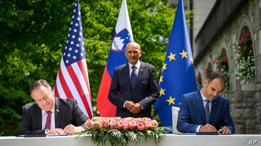 US Secretary of State Mike Pompeo, left, and Slovenia's Foreign Minister Anze Logar sign an agreement on fifth-generation internet technology as Slovenia's Prime Minister Janez Jansa stands at center, in Bled, Slovenia, Aug. 13, 2020.