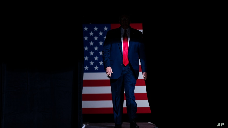 FILE - President Donald Trump arrives on stage to speak at a campaign rally at the BOK Center in Tulsa, Oklahoma, June 20, 2020.